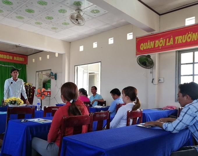 Bí thư Đảng ủy xã Thừa Đức Trần Trung Kiên (đứng) trao đổi với các hộ dân tham gia dự án. - Ảnh LT