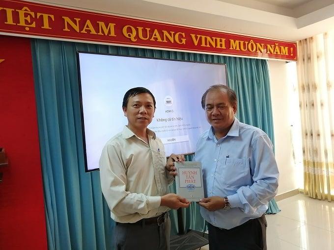 Ông Phạm Văn Luân (trái)trao tặng sách cho ông Lê Văn Nhường - Ảnh STT.